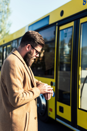 side view of bearded man checking time while standing on bus stop Zdjęcie Seryjne
