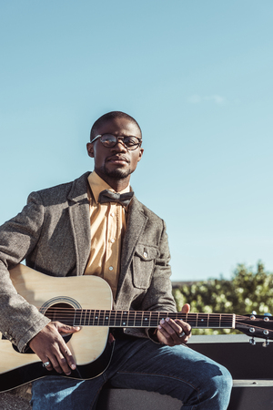 Handsome african american man in stylish clothes, posing with guitar