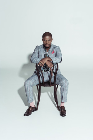 Handsome african american man sitting on chair backwards and looking at camera