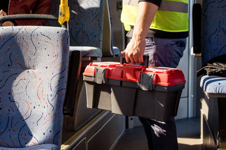 partial view of worker with toolkit in hand riding in public transport