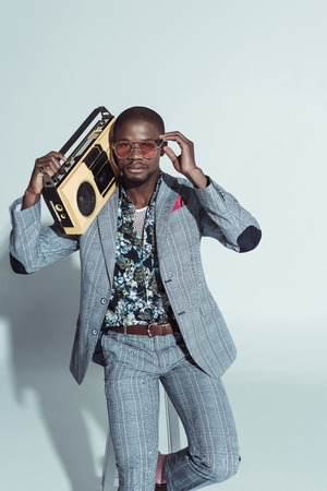 Stylish african american man in a suit, holding a boombox and putting on sunglasses Standard-Bild - 102348738