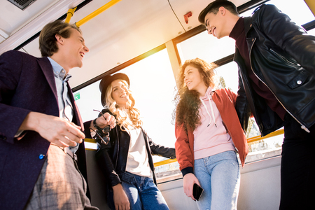 low angle view of smiling young friends talking while standing together in city bus