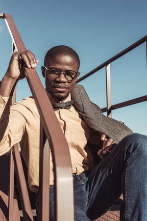 Stylish african american man sitting on metal stairs and looking at camera Stock Photo