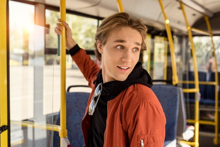 portrait of smiling man holding bus handle while riding in public transport Imagens
