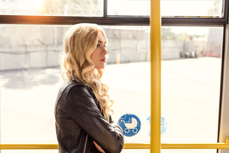 side view of pensive woman with arms crossed looking away while riding in city bus Imagens