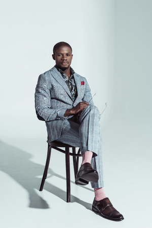 Sophisticated african american man in suit, sitting on chair with legs crossed and looking at camera Imagens