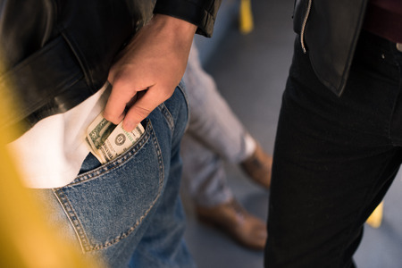 cropped shot of man stealing money in public transport