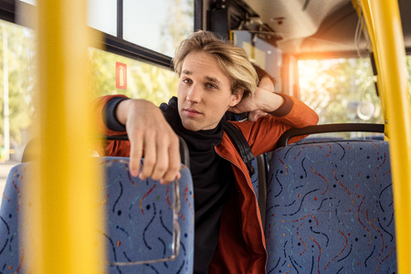 thoughtful man sitting on bus seat while riding in public transport Stockfoto