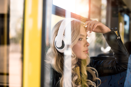 pensive young woman in headphones listening music in bus