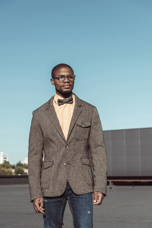 Handsome african american man in tweed jacket and glasses, standing in urban setting