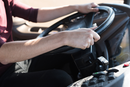 cropped shot of bus driver holding steering wheel