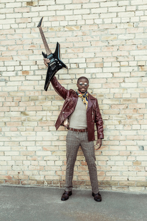 Young african american man wearing stylish clothes and sunglasses, holding an electrical guitar in outstreched arm