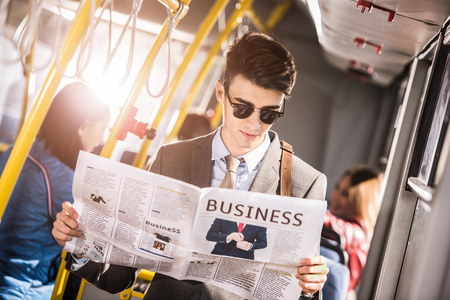 Beau jeune homme d'affaires à lunettes de soleil lisant le journal en bus