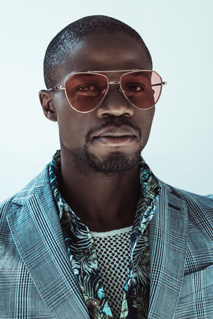 Portrait of handsome african american man in stylish clothes and sunglasses, looking at camera