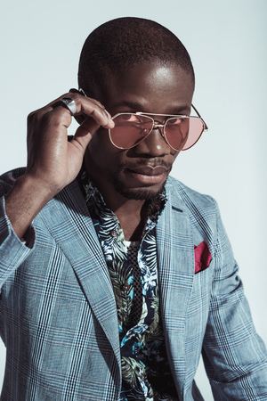 Fashionable african american man in suit, looking at camera over sunglasses, isolated on grey