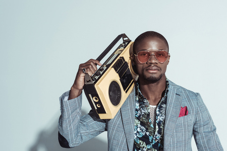 Young african american man in suit and sunglasses, holding a boombox and looking at camera Stock Photo