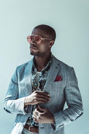 Young african american man in fashionable suit and sunglasses, posing with hand on one side of his jacket 写真素材