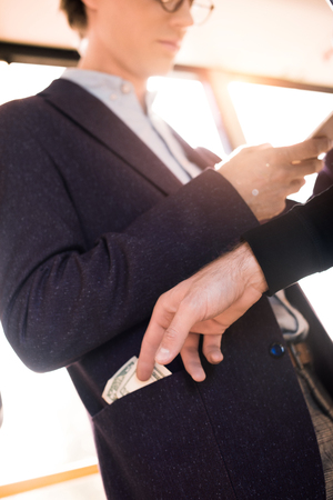 cropped shot of person stealing money from pocket of businessman in bus Stok Fotoğraf