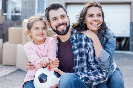 happy young family sitting in front of new house