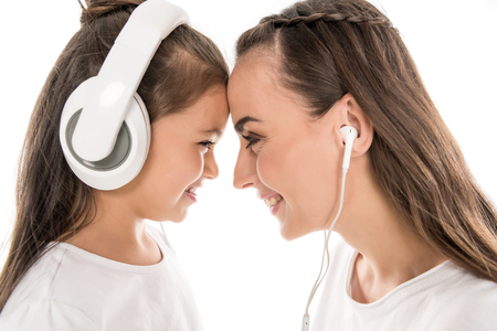 mother and daughter listening music with headphones and earphones, isolated on white Stock Photo