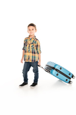 happy little boy with suitcase ready for journey, isolated on white Stockfoto