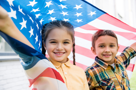 smiling brother and sister with american flag Stock Photo