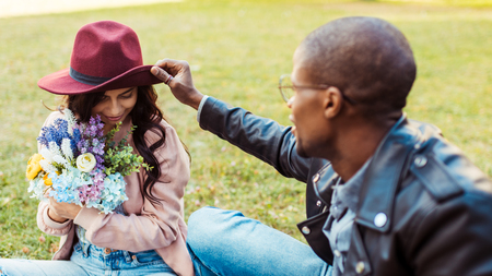 Girlfriend sitting with flowers and her boyfriend touching her hat in the park