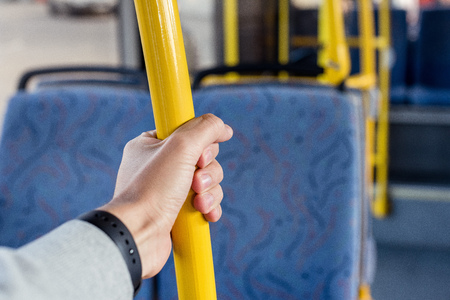 partial view of male hand holding bus handle