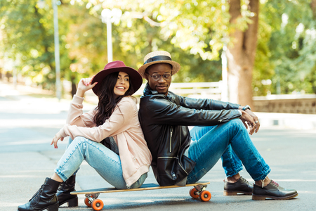 Happy multicultural couple in hats sitting on a longboard on a street