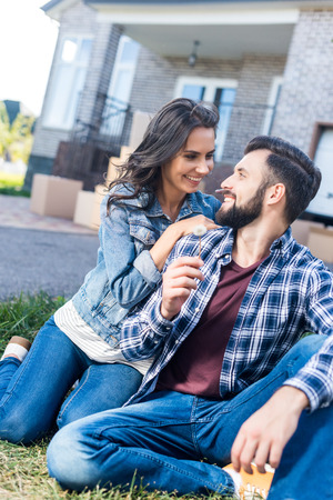 young couple with dandelion flower in garden of new house