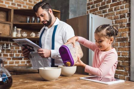 happy little daughter pouring cereal in bowl for father on breakfast