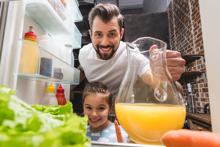 happy young father and adorable daughter taking juice from fridge