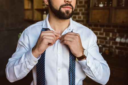 cropped shot of businessman fastening buttons on shirt at kitchen Stock Photo