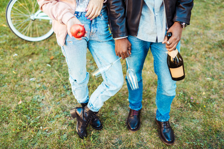 Cropped image of Couple standing with apple, glasses and champagne in the park