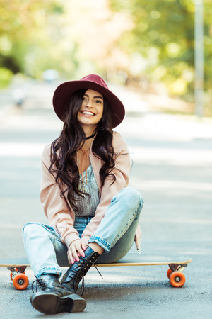 Smiling woman sitting on a longboard and looking at camera
