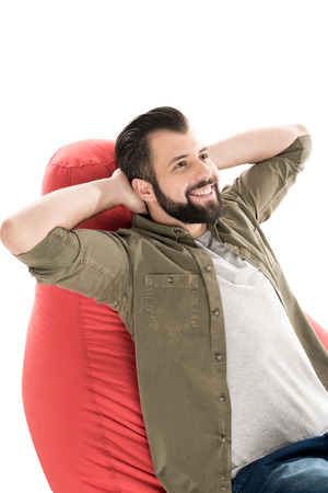 man relaxing on bean bag chair, isolated on white Stock Photo