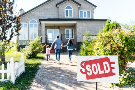 family moving into new house with sold signboard on foreground Banque d'images - 102351174