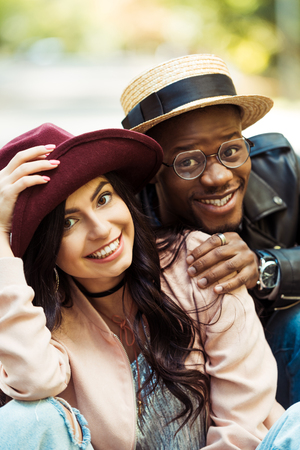 Portrait of smiling multicultural couple in hats  Stock Photo