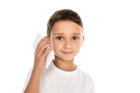 portrait of smiling little boy looking at camera while talking on smartphone isolated on white Stock Photo
