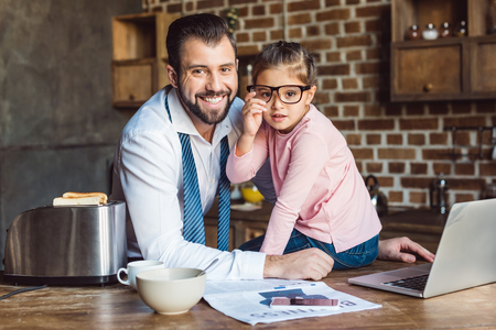 father and daughter sitting on kitchen with laptop and newspaper on table Stock Photo
