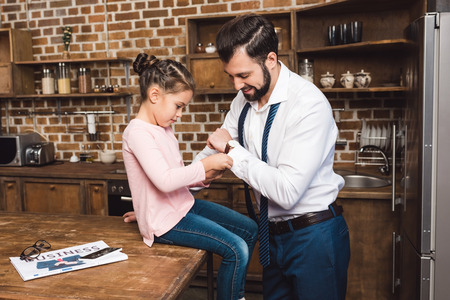happy little daughter fixing cufflinks for father on kitchen 스톡 콘텐츠