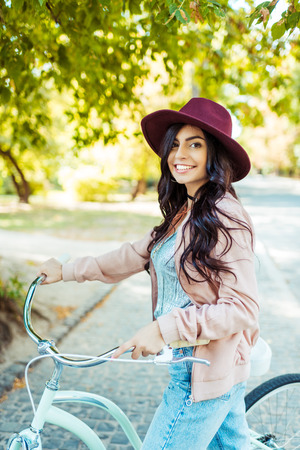 Beautiful smiling woman in hat standing with a bicycle Reklamní fotografie
