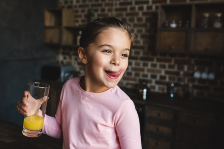 adorable happy child drinking orange juice and licking lips Stock Photo