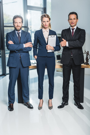 lawyers with arms crossed standing near colleague that holding contract in office