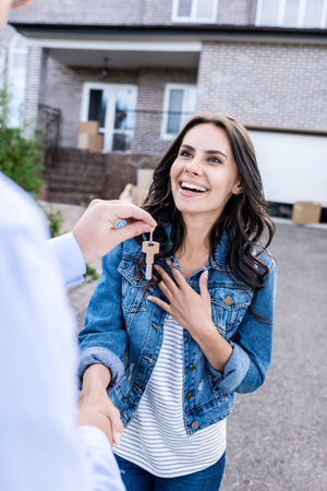 close-up shot of young woman buying new house and shaking hands with realtor