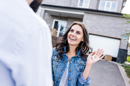 surprised young woman looking at man with keys in hand Stock Photo