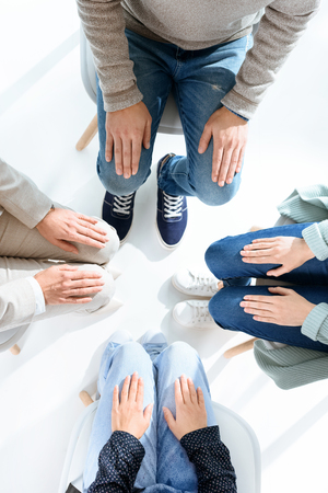 top view of people sitting with hands in knees at group therapy session