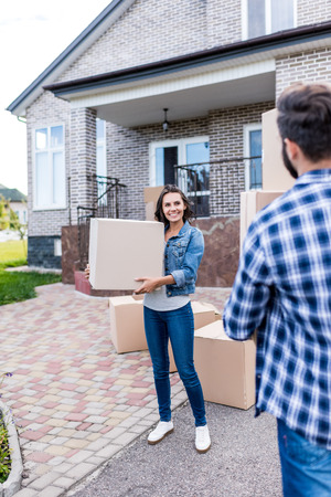 young beautiful couple with boxes moving into new house Stock Photo