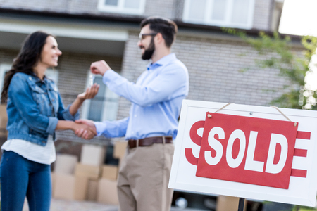 woman buying new house with sold signboard on foreground Standard-Bild