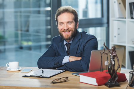 portrait of smiling lawyer looking at camera while sitting at workplace with contract in office